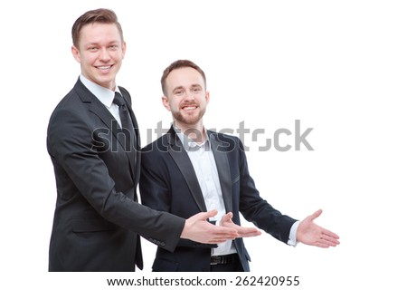Advertising your product. Two happy young businessmen pointing copy space and smiling at camera while standing isolated on white - stock photo
