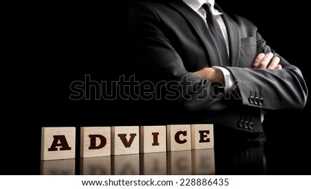 Advice Letters on Arrange Small Wooden Pieces with Confident Businessman Crossing Arms in Front of the Body. Captured on Black Background. - stock photo