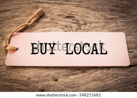 advice to Buy Local printed on a pink paper price tag  - stock photo