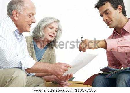 Advisor explaining paperwork to an elderly grey-haired retired couple seated on a couch - stock photo