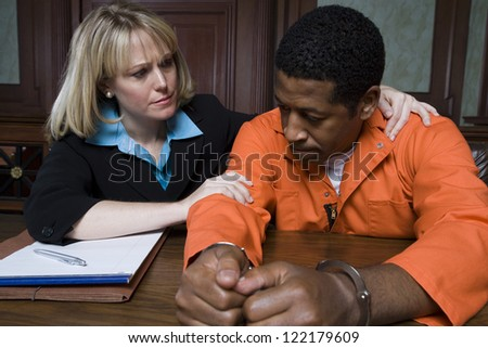 Advocate and prisoner in handcuffs listening case in courtroom - stock photo