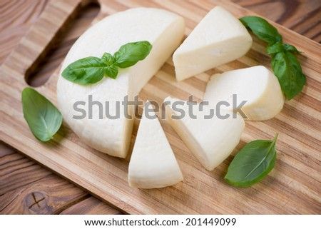 Adygea cheese with fresh basil, high angle view, studio shot - stock photo