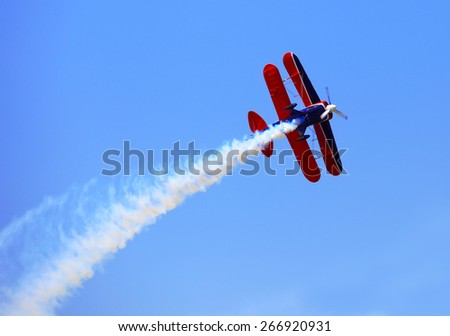 Aerial acrobatics - red propeller plane with smoke trail against clear blue sky - stock photo