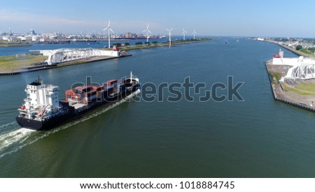 Aerial bird view photo of container ship moving through Maeslantkering storm surge barrier on Nieuwe Waterweg Netherlands it closes if Rotterdam is threatened by floods and is part of Delta Works