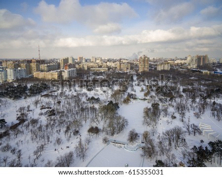 Aerial camera captures snow covered pine trees in Victory Park Odessa. The Odessa city skyline is in the background