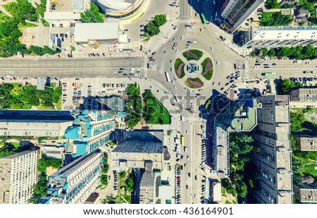 Aerial city view with crossroads and roads, houses, buildings, parks and parking lots, bridges. Urban landscape. Copter shot. Panoramic image.
