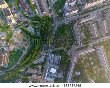 Aerial city view with crossroads, roads, houses, buildings, parks, parking lots, bridges - stock photo