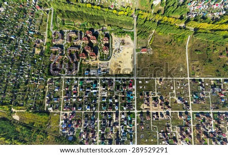 Aerial city view with crossroads, roads, houses, buildings, parks, parking lots, bridges - stock photo