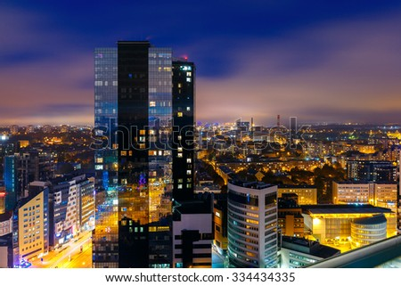 Aerial cityscape of modern business financial district with tall skyscraper buildings illuminated at night, Tallinn, Estonia - stock photo