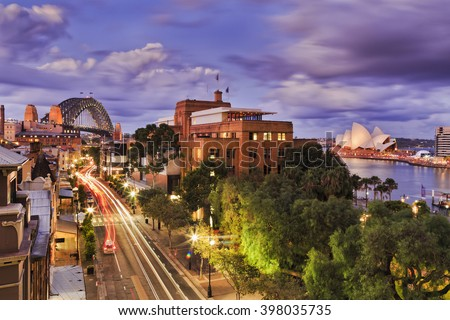 Aerial elevated view of The Rocks historic district in Sydney CBD as Sunset when bright lights illuminate city streets and landmarks. - stock photo