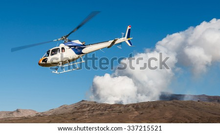 Aerial Flying Unidentified Emergency Tourist Rescue Helicopter with Out of Focus Danger Mount Aso Active Volcano Crater Eruption Hot Smoke Steam on Sunny Clear Blue Sky, Kumamoto, Kyushu Island, Japan - stock photo
