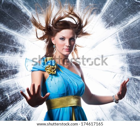 Aerial girl in blue dress on a surreal silver background