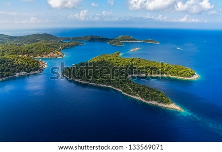 Aerial helicopter shoot of National park on island Mljet, village Pomena, Dubrovnik archipelago, Croatia. The oldest pine forest in Europe preserved. - stock photo