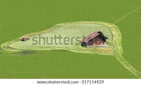 Aerial image of a green agricultural field with working mowing machine in circle around a wooden house. The meadow is filled the frame and the objects are in the center. - stock photo