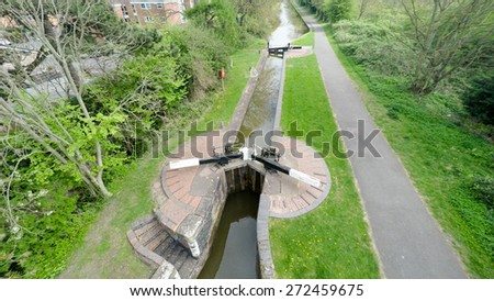 Aerial image of a peaceful canal lock with a small towpath along side. - stock photo