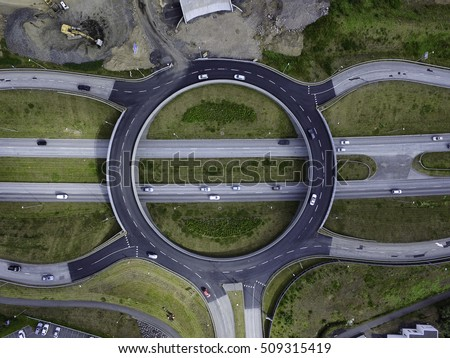Aerial image of a roundabout over a 4 lane highway, cars on the road and road construction to the side