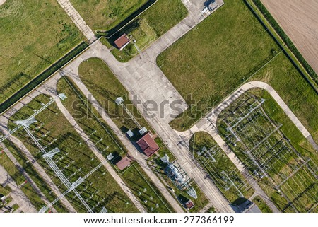 Aerial image of electrical substation featuring wires, transformers and large scale power energy towers in Poland - stock photo