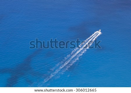 Aerial image of motorboat floating in a turquoise blue sea water. The boat is moving diagonally through the frame of the photo.  - stock photo