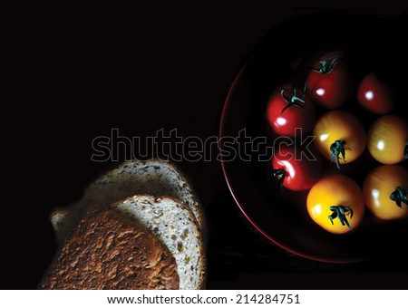 Aerial image of selectively lit amber & rosso vine tomatoes with sliced granary bread against black. Copy space. - stock photo