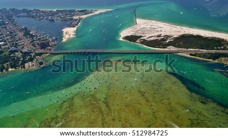 Aerial image of the Destin Harbor in Destin, FL, showing the East Pass, Crab Island, and the Marler Bridge.