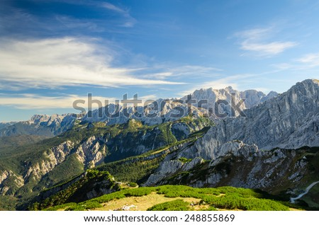 Aerial landscape view of summer Alps sunlight high mountain peaks with green valley and deep blue sky - stock photo