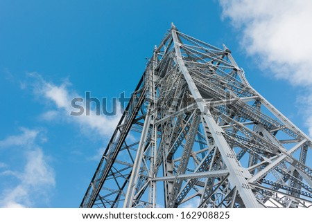Aerial Lift Bridge Steel Structure on a Blue and Cloudy Sky - stock photo