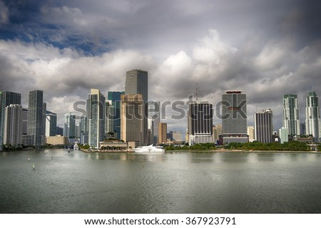 Aerial marine view of high skyscrapers with dark grey cloudy sky, white boat standing next to downtown, horizontal picture - stock photo