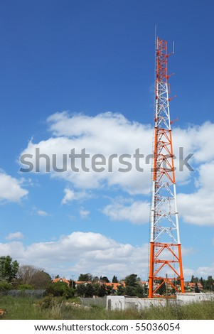 Aerial metallic red and white mast in the small village - stock photo