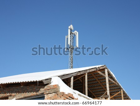 Aerial mobile communication on a roof of the old house against the blue sky - stock photo