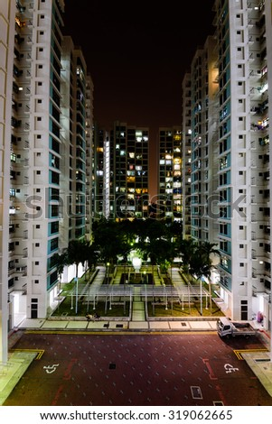 Aerial new estate with neighborhood faculties car park and green garden at the center at Eunos area of Singapore. Night view - stock photo
