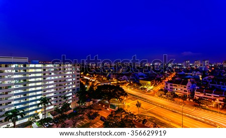 Aerial night view of new estate, HDB housing complex near the highway in Eunos area, Singapore. Blue hour view. Urban motion concept. Panoramic style - stock photo