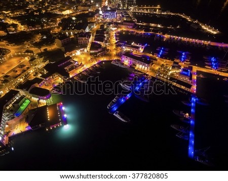 Aerial night view of the beautiful Marina in Limassol city in Cyprus. A very modern, high end and newly developed area where yachts are moored and it's perfect for a waterfront promenade.  - stock photo