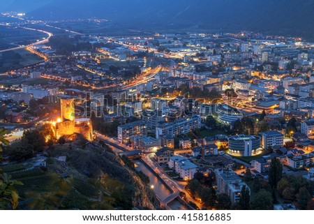 Aerial night view of the town of Martigny in Valais, Switzerland. Chateau de la Batiaz is overlooking the scene. - stock photo