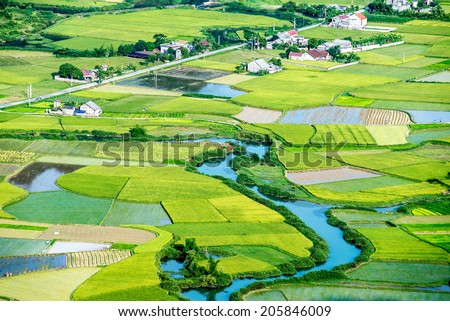 Aerial of a village with rice field and a river running through - stock photo