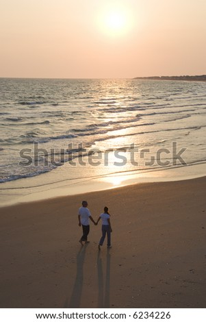 Aerial of couple holding hands and walking on beach on Bald Head Island, North Carolina. - stock photo