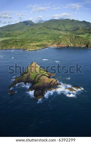 Aerial of rock jutting out of Pacific ocean off the coast of Maui, Hawaii with mountain landscape in background.