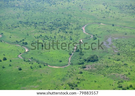 Aerial of savannah type vegetation in Africa, with a river, shot over South Sudan in the rainy season - stock photo