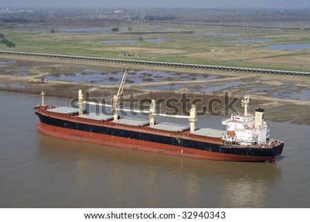 Aerial of single cargo ship at anchor in Mississippi River - stock photo