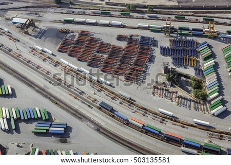 Aerial of unloading container trailers at railway terminal, USA. Railroad tracks, containers, trailers