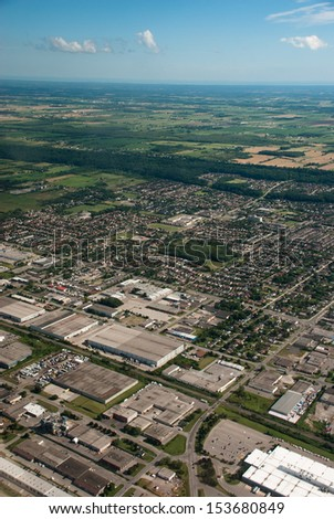 Aerial of warehouses beside residential houses - stock photo