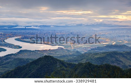 Aerial panorama of beautiful Taipei City in morning twilight with a fascinating view of Kuandu plain, Tamsui River and Taipei 101 in downtown area ~ A blue and misty morning in Taipei, Taiwan - stock photo