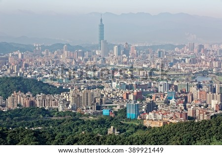 Aerial panorama of busy Taipei City with view of Taipei 101 Tower in downtown area, Keelung River and distant Mountains in morning light ~ Scenery of Taipei City under morning sunshine - stock photo