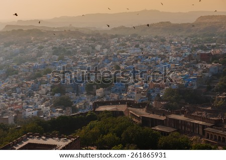 """Aerial panorama of Jodhpurs, also known as """"Blue City"""" due to the vivid blue-painted Brahmin houses. View from Mehrangarh Fort (part of fortifications is also visible). Jodphur, Rajasthan, India - stock photo"""