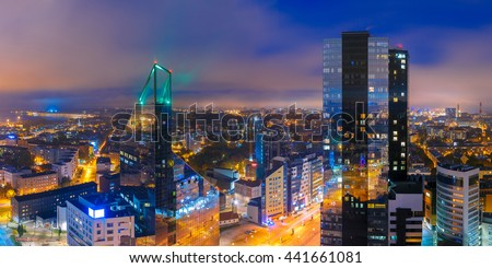 Aerial panorama of modern business financial district with tall skyscraper buildings illuminated at night, Tallinn, Estonia - stock photo