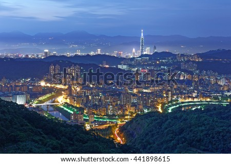 Aerial panorama of overpopulated suburban communities in Taipei at dusk with view of Taipei buildings in downtown & bridges over Xindian River ~ A romantic evening of Taipei in beautiful blue twilight - stock photo