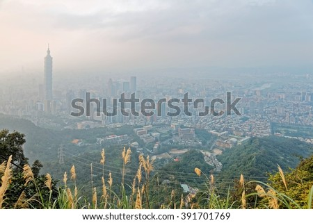 Aerial panorama of Taipei City at foggy dusk with view of Taipei 101 Tower in downtown area, Tamsui River and distant Mountains in the background ~ Scenery of Taipei City under misty sunset sunshine - stock photo
