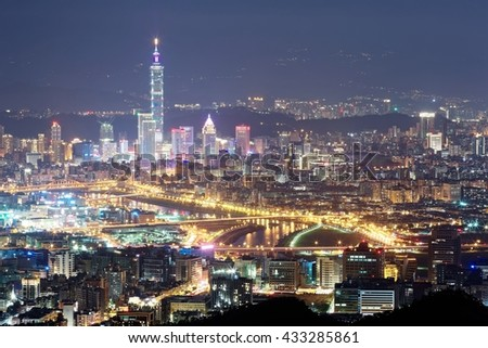 Aerial panorama of Taipei City at night with view of bridges over Keelung River & Taipei 101 Tower among skyscrapers in Xinyi District Downtown~Romantic nightscape of a busy city in a gloomy blue mood