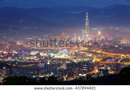 Aerial panorama of Taipei City Downtown at night with view of Taipei 101 Tower among skyscrapers in Xinyi District, bridges over Keelung River & mountain silhouettes in the background in blue twilight