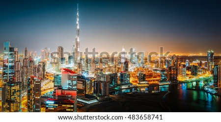 Aerial panorama view of a big futuristic city by night. Business bay, Dubai, United Arab Emirates. Dark colorful nighttime skyline.