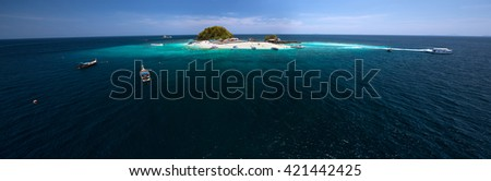 Aerial panoramic shot of the tropical island in the middle of the sea with blue clear water.